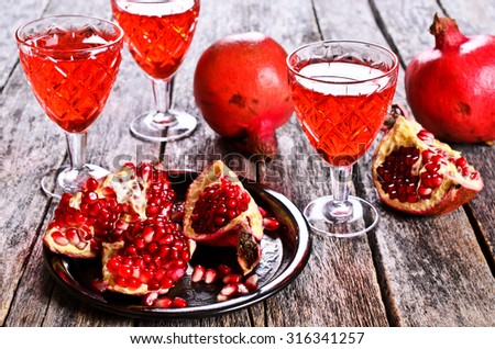 Pomegranate, cut into sections on a metal dish in the background of the shot glasses with red drink - stock photo
