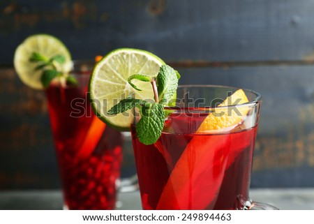 Pomegranate drink in glasses with mint and slices of orange and lime on color wooden background - stock photo