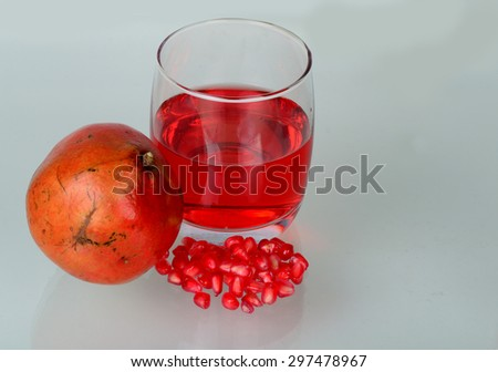 Pomegranate juice in a glass and ripe pomegranate seeds in glass bowl. - stock photo
