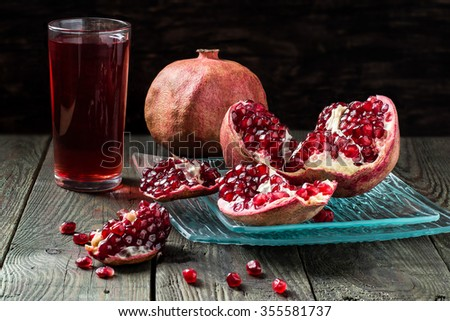 Pomegranate juice in a glass and slices of ripe pomegranate with grains on the wooden table. Selective focus - stock photo