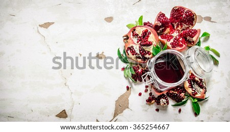 Pomegranate juice with bits of pomegranates and leaves. On rustic background. Free space for text . Top view - stock photo