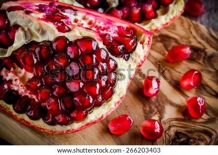 Pomegranate open with seeds on wooden cutting board - stock photo