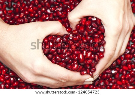 Pomegranate seed's pile raked up to heart form by woman hands - stock photo