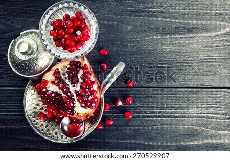 Pomegranate slice and grains close up. Dark wooden table. Silver tableware. Toned. - stock photo
