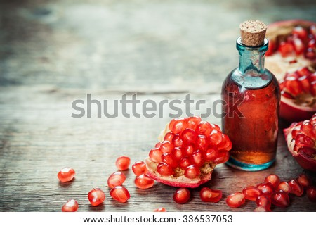Pomegranate tincture or  juice and red ripe garnet fruit with seeds on wooden table. Selective focus. - stock photo
