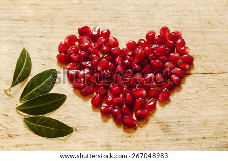 pomegranate with seeds and leaves - stock photo