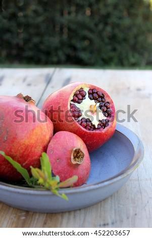 Pomegranates on Blue Pottery Dish 2 - stock photo