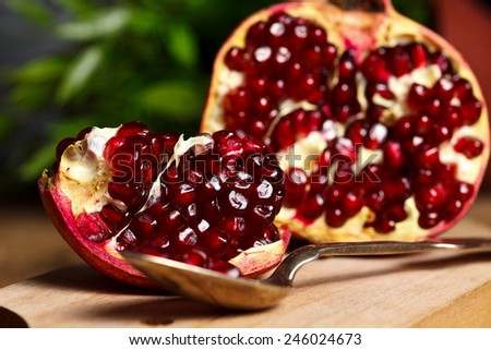 Pomegranates with silver teaspoon on wooden cutting board - stock photo