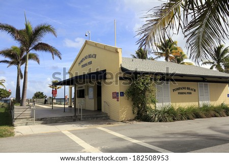 POMPANO BEACH, FLORIDA - DECEMBER 22, 2013: Entrance to wooden 1,000 foot length Pompano Beach Municipal Fishing Pier with concession stand and restrooms building on the right on a sunny tropical day  - stock photo