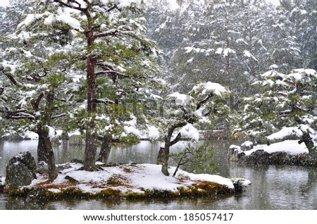 Pond at Kinkakuji, Kyoto in Japan. A snowy scene with snow covered pine trees on tiny islands.  - stock photo