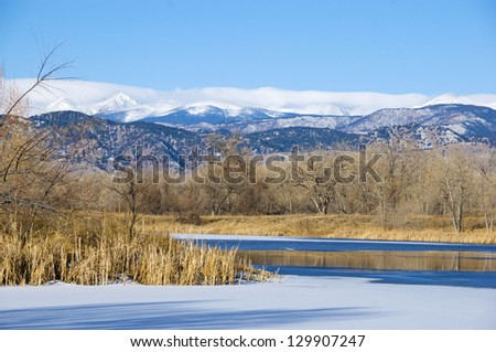 Pond in a wetlands area on the Colorado prairie, with view of the Rocky Mountain Continental Divide. - stock photo