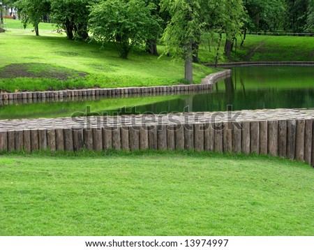 Pond in park with wooden water dam - stock photo
