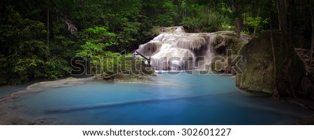 Pond with clear blue water and waterfall in Thailand rainforest. Panoramic nature background  - stock photo