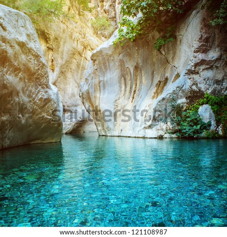 Pond with clear blue water in mountain - stock photo