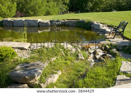 Pond with water falls and bench - stock photo