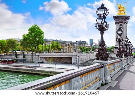 Pont Alexandre III bridge (1896) spanning the river Seine. Decorated with ornate Art Nouveau lamps and sculptures .Paris. - stock photo