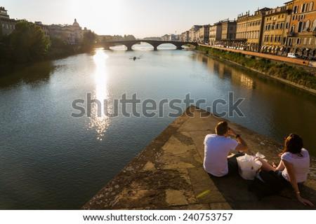 Ponte alla Carraia medieval Bridge landmark on Arno river, sunset landscape with reflection. - stock photo