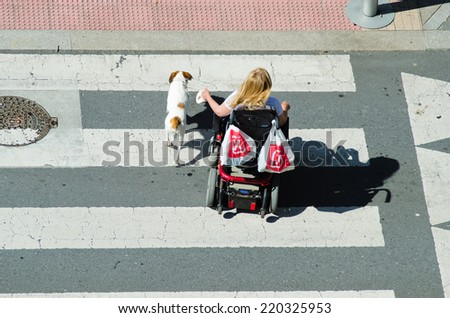PONTEVEDRA, SPAIN - JUNE 13, 2014: A woman in a wheelchair and accompanied by a dog, go on a pedestrian crossing. - stock photo