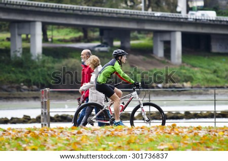 PONTEVEDRA, SPAIN - NOVEMBER 23, 2014: A man practices cycling, while crossing a couple strolling along the promenade near the river which crosses the city .. - stock photo