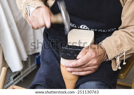 PONTEVEDRA, SPAIN - SEPTEMBER 6, 2014: A shoemaker manufactures boots, in medieval festival held each year in the historical district of the city. - stock photo