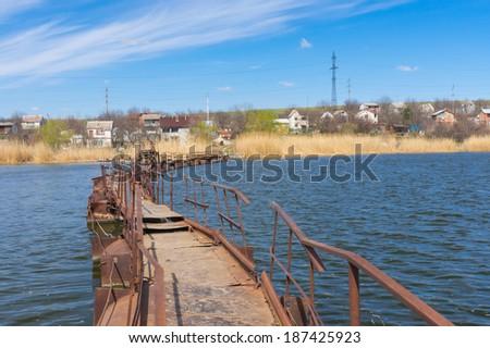 Pontoon bridge over small river to remote Ukrainian village - stock photo
