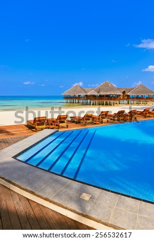 Pool and cafe on Maldives beach - nature vacation background - stock photo