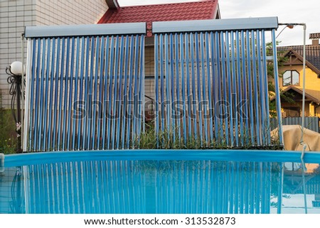 Pool and solar collectors for water heating. Home pool in the backyard. Modern heating water. The stylish light manifold.  - stock photo