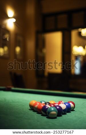pool balls on billiards table in cozy dark bar - stock photo