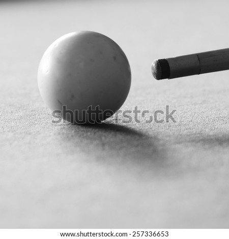 Pool cue and the white ball in shallow focus on a pool table in black and white - stock photo
