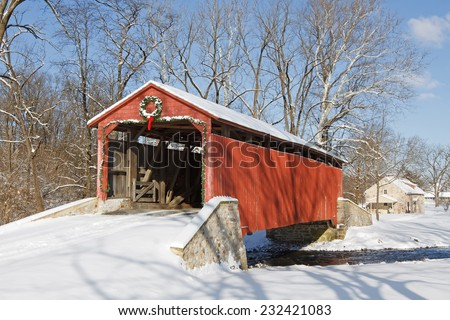 Pool Forge Covered Bridge with snow on a bright winter day in Lancaster County, Pennsylvania, USA. - stock photo