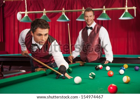 Pool game. Confident young man aiming the billiard ball with cue while his opponent smiling on the background - stock photo