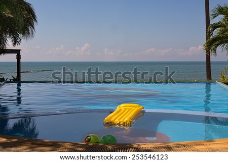 Pool overlooking the sea with yellow inflatable mattress. - stock photo