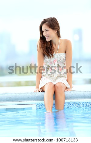Pool woman relaxing sitting in summer dress with legs in pool smiling happy with skyline in background. Beautiful mixed race Asian Chinese / Caucasian girl. - stock photo