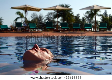 Poolside A young woman is relaxing in the pool. Ideal vacation shot with sun umbrellas and palm trees in the back. - stock photo
