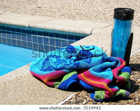 Poolside towel and drink - stock photo