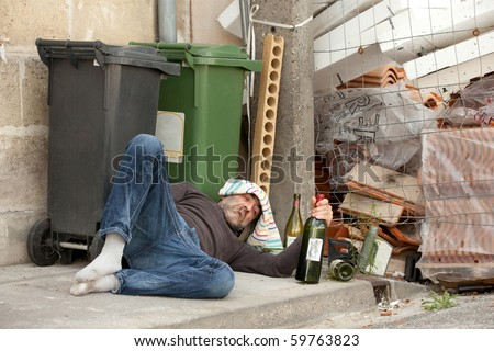 poor and drunk man lying on sidewalk  with bottles of wine near trash can - stock photo