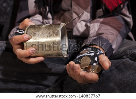 Poor beggar child counting coins - closeup on dirty hands holding tin can - stock photo