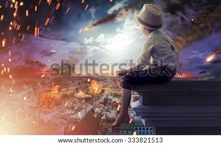 Poor boy looking at fire disaster - stock photo