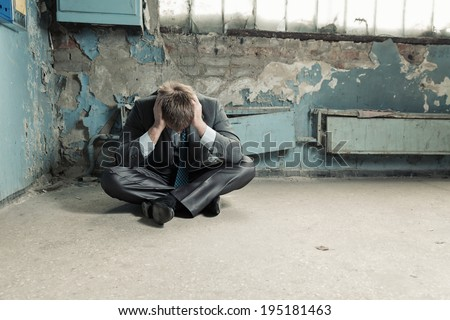 Poor businessman sitting on old cellar - stock photo