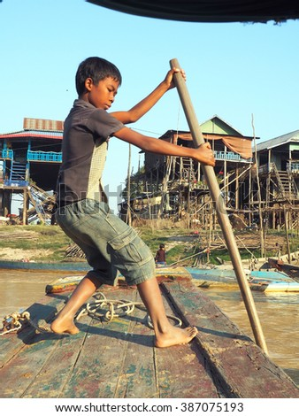 poor cambodian boy working on a boat in floating village - stock photo