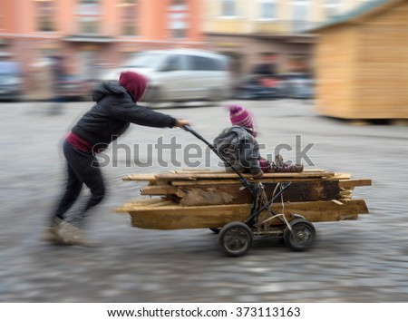 Poor children pushing wheelbarrow with firewood for winter - stock photo