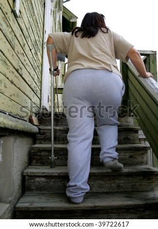 Poor fat disabled woman entering her shabby old house. - stock photo