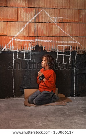 Poor homeless beggar boy praying for a shelter concept - kneeling on cardboard - stock photo