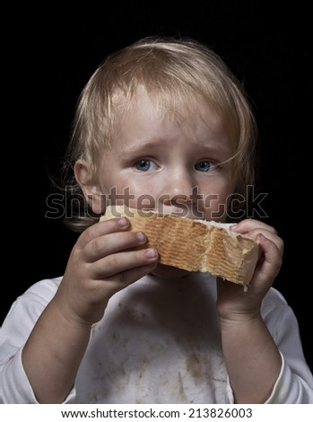 poor hungry child eating bread - stock photo