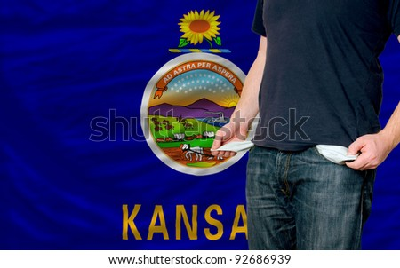 poor man showing empty pockets in front of american state of kansas flag - stock photo