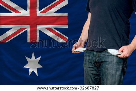 poor man showing empty pockets in front of australia flag - stock photo