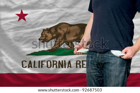 poor man showing empty pockets in front of california flag - stock photo