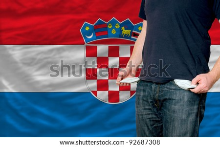 poor man showing empty pockets in front of croatia flag - stock photo