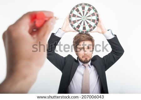 Poor man standing with the dartboard on his head waiting of hitting the target - stock photo