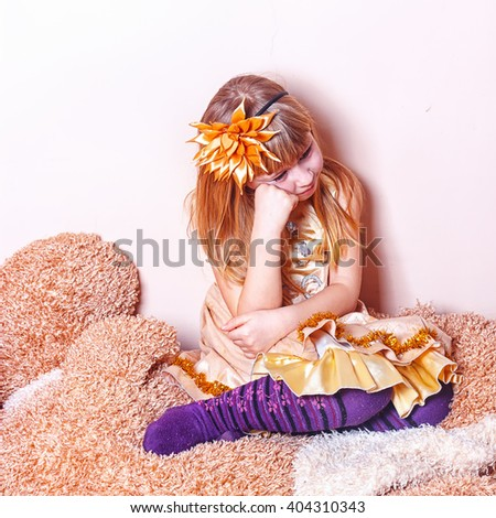 poor, sad little child girl sitting against the concrete wall - stock photo